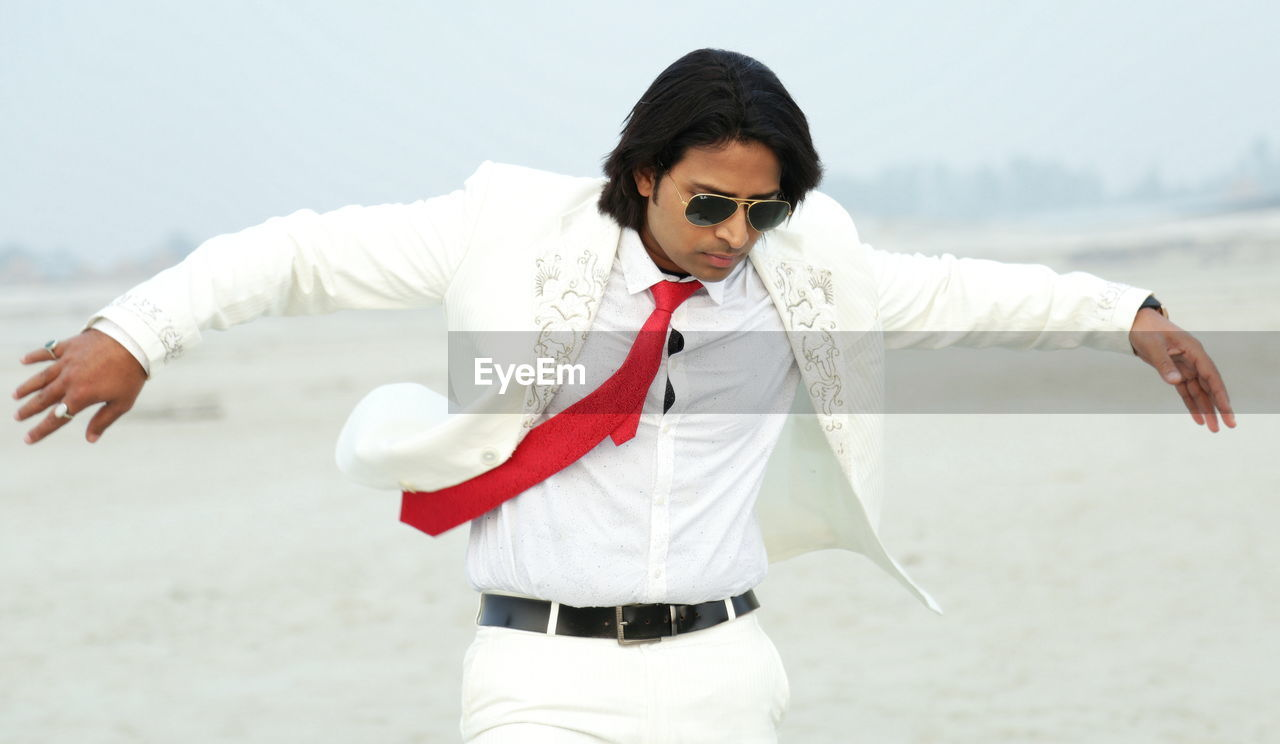 Man wearing white suit on the beach