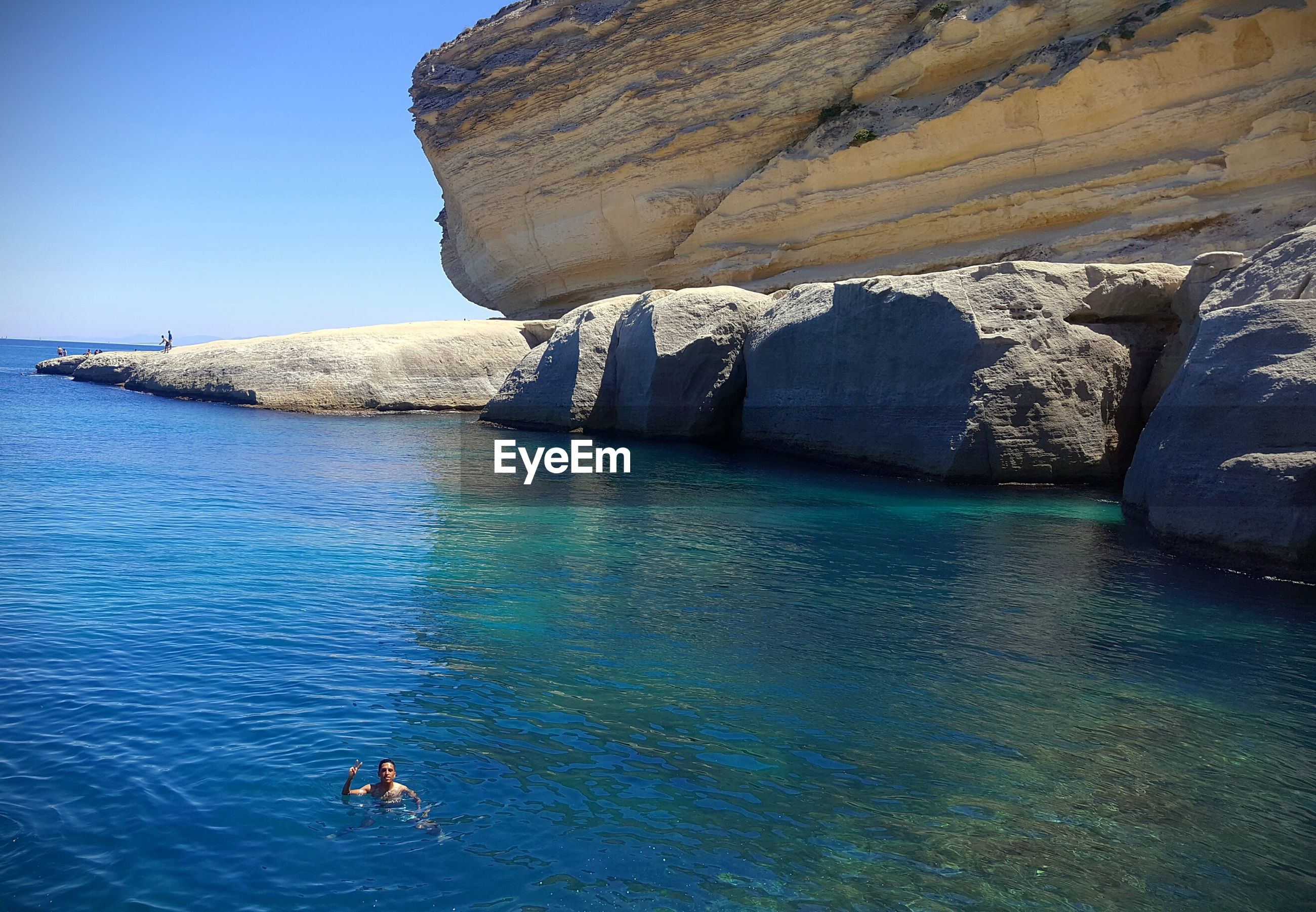 Man swimming in sea against rock formation