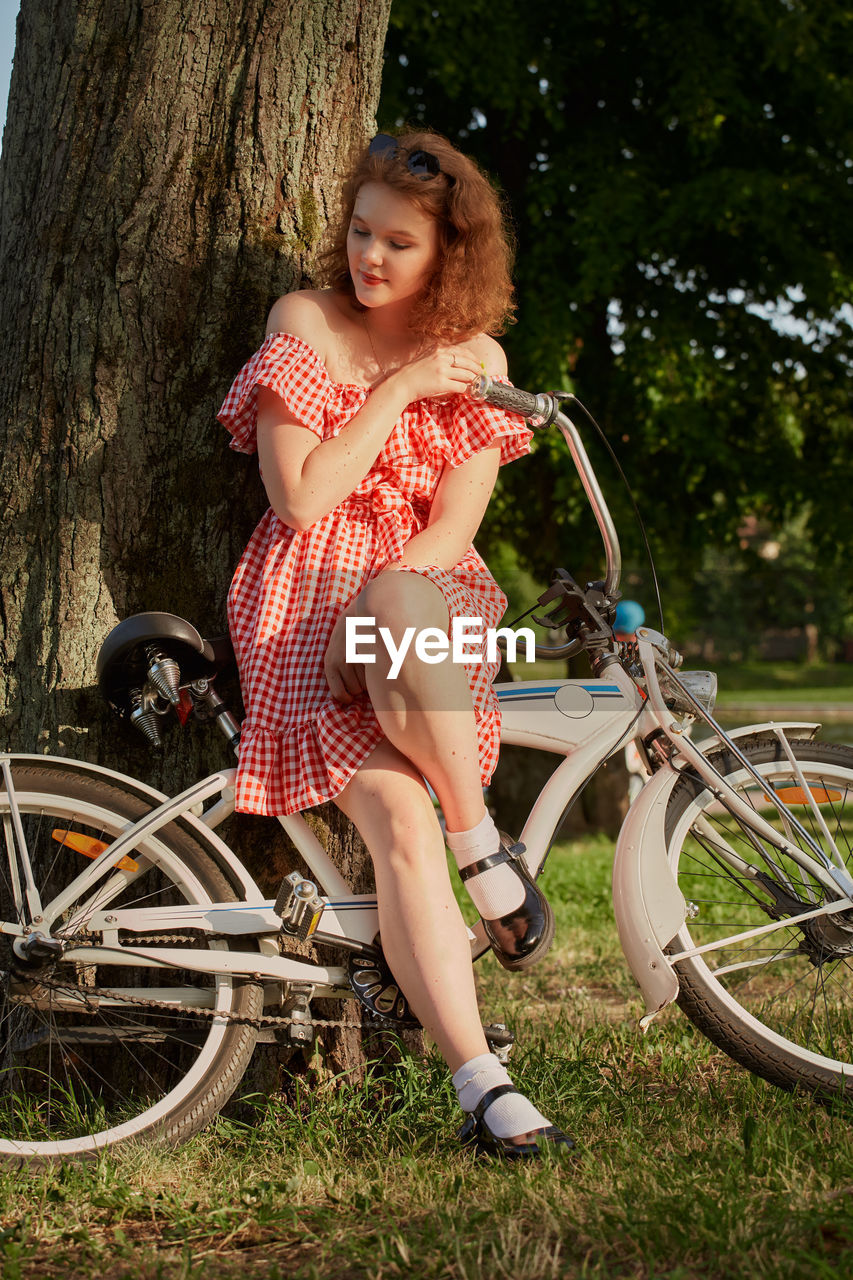 WOMAN SITTING ON BICYCLE AGAINST TREES