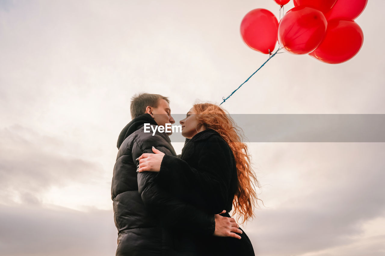 Low angle view of couple embracing against sky