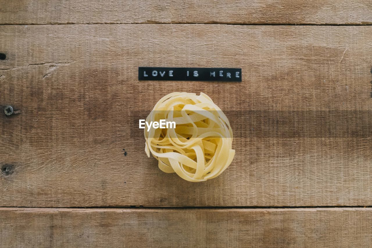 pasta, italian food, indoors, wood - material, directly above, no people, freshness, food and drink, food, close-up, yellow, table, wellbeing, text, raw food, still life, spaghetti, high angle view, preparation, wood grain