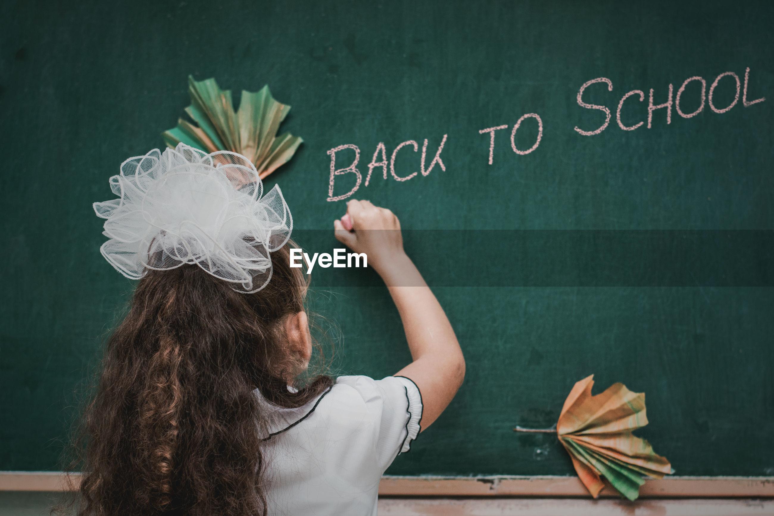 Rear view of girl writing on blackboard in school