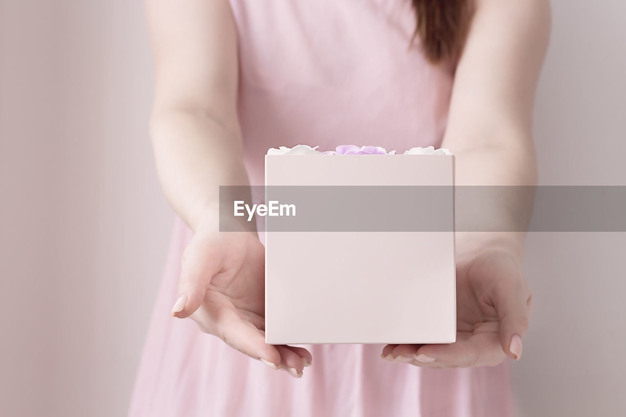 MIDSECTION OF A WOMAN HOLDING PAPER IN BOX