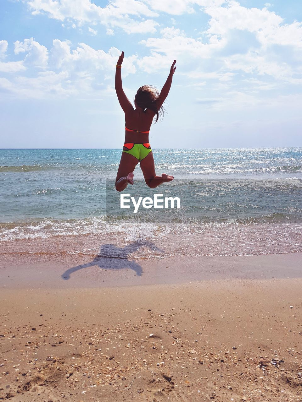 Rear View Of Young Woman Jumping At Beach Against Sky