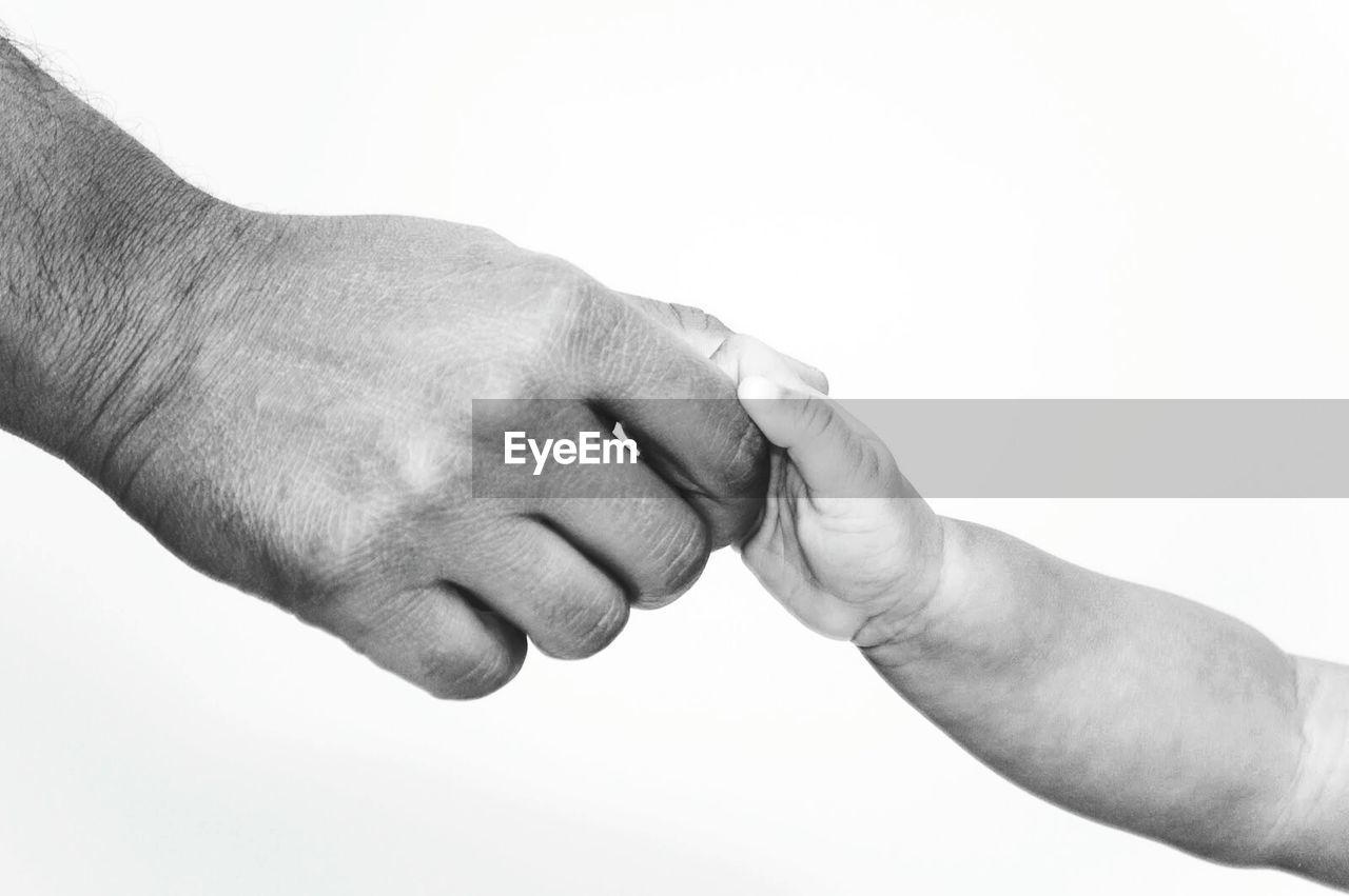 Cropped Image Of Father Holding Son Against White Background