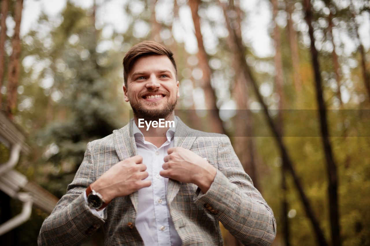 Low angle view of businessman smiling while standing against trees