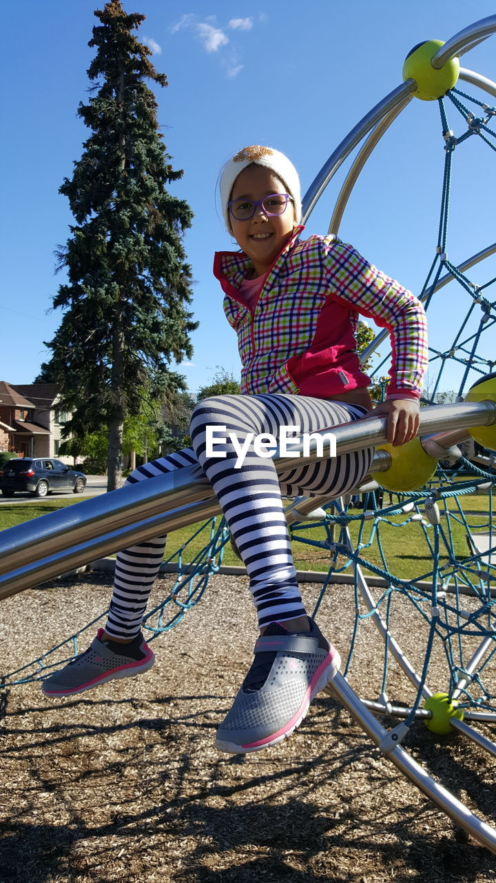 playground, childhood, leisure activity, casual clothing, full length, one person, real people, lifestyles, park - man made space, front view, happiness, outdoors, day, striped, elementary age, tree, smiling, fun, looking at camera, girls, low angle view, outdoor play equipment, young women, young adult, clear sky, portrait, sky