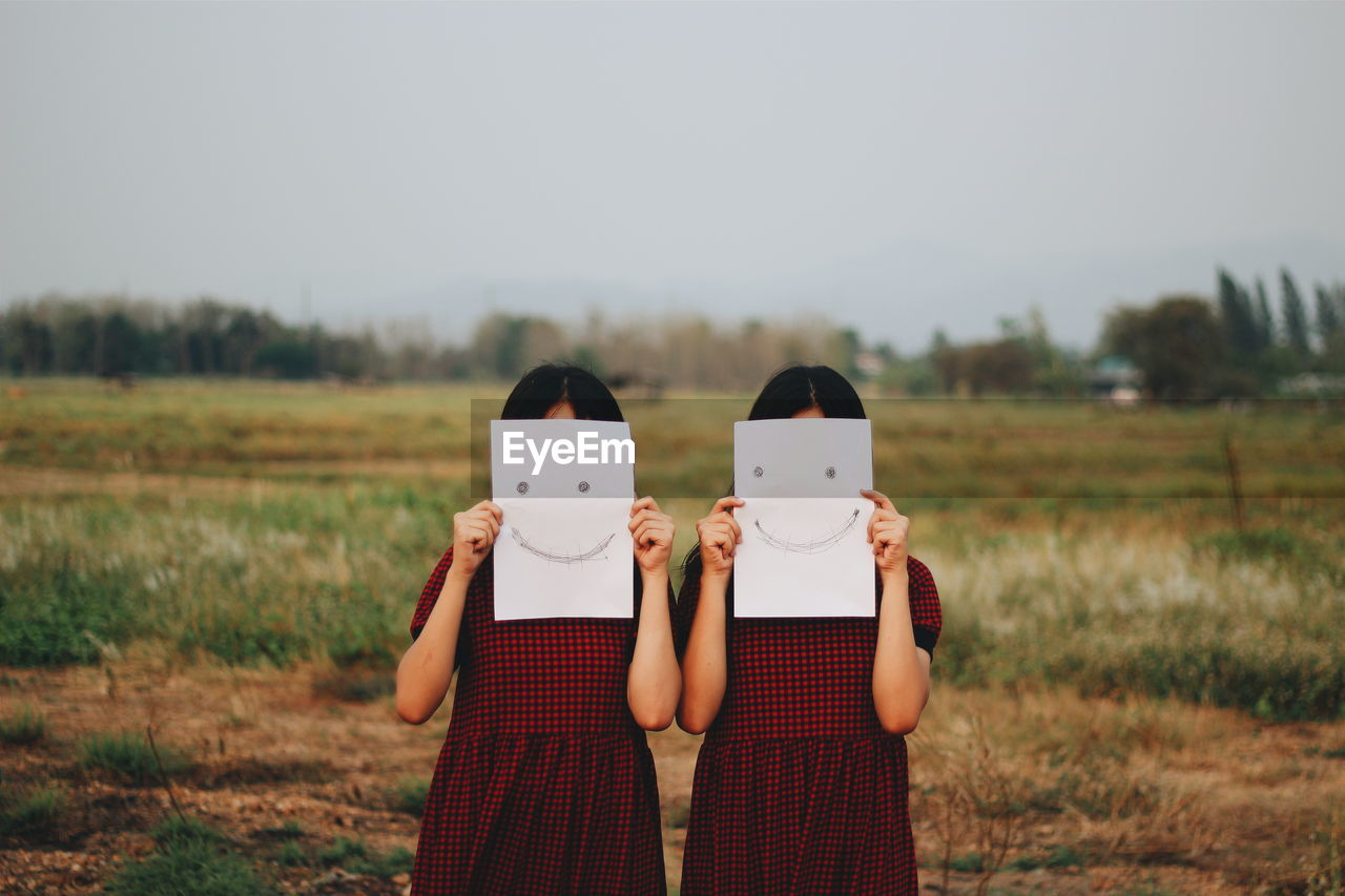 Girls Holding Smiley Face Drawn Papers In Front Of Face On Field