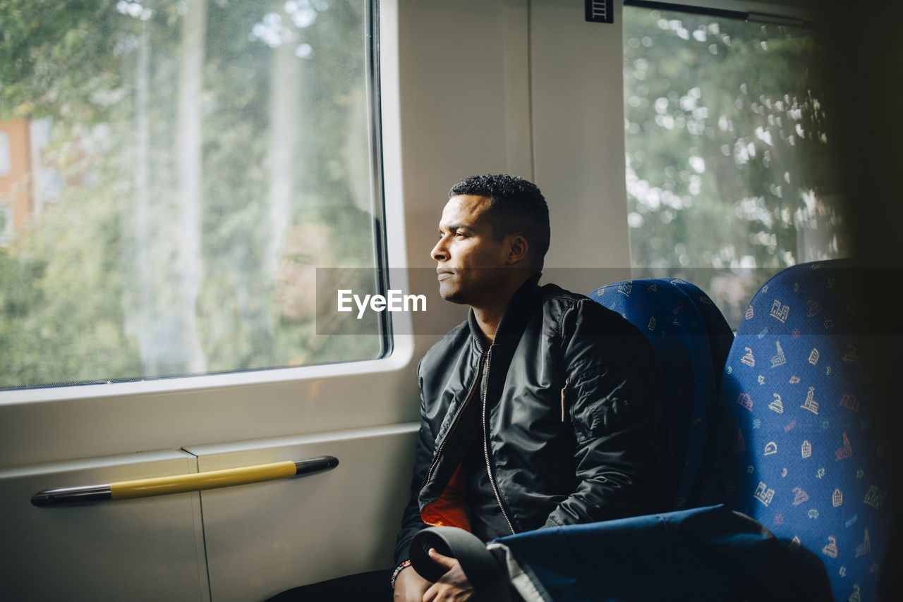 window, one person, real people, sitting, looking, waist up, men, young men, day, looking away, indoors, seat, lifestyles, males, mode of transportation, leisure activity, train, young adult, contemplation
