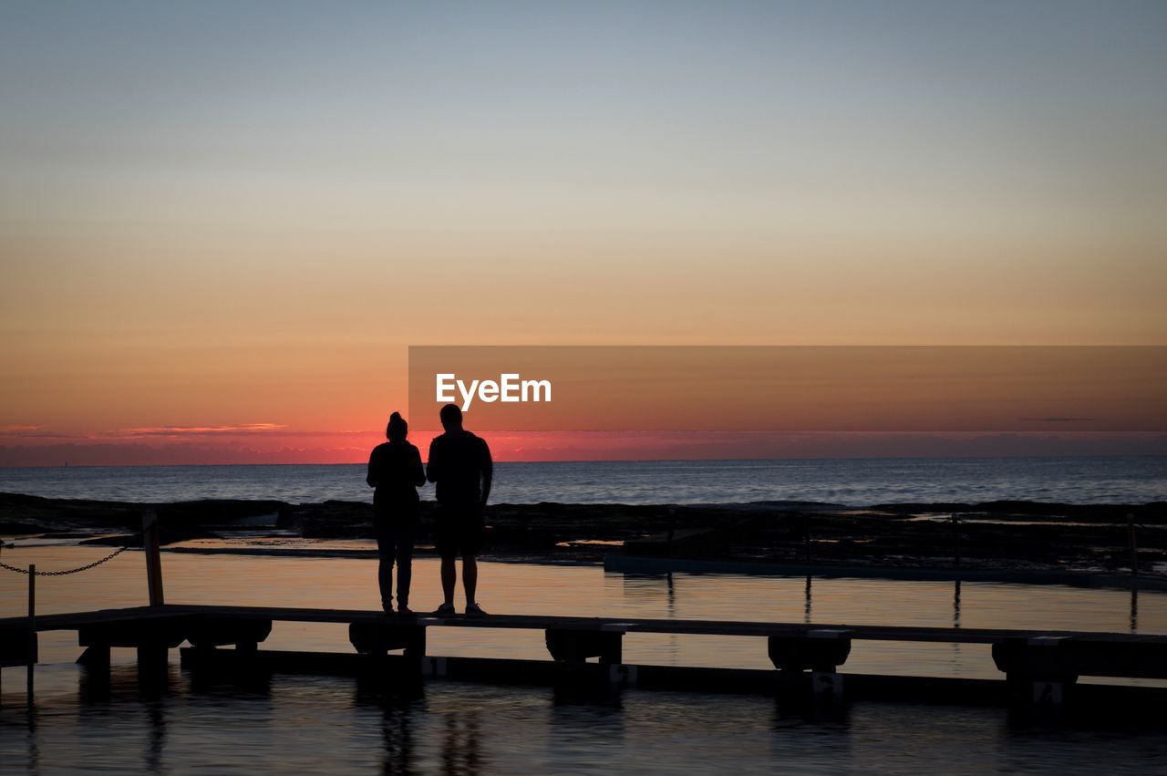 sea, sunset, water, silhouette, horizon over water, beauty in nature, two people, scenics, men, nature, real people, tranquil scene, leisure activity, standing, sky, full length, togetherness, outdoors, friendship, day, people