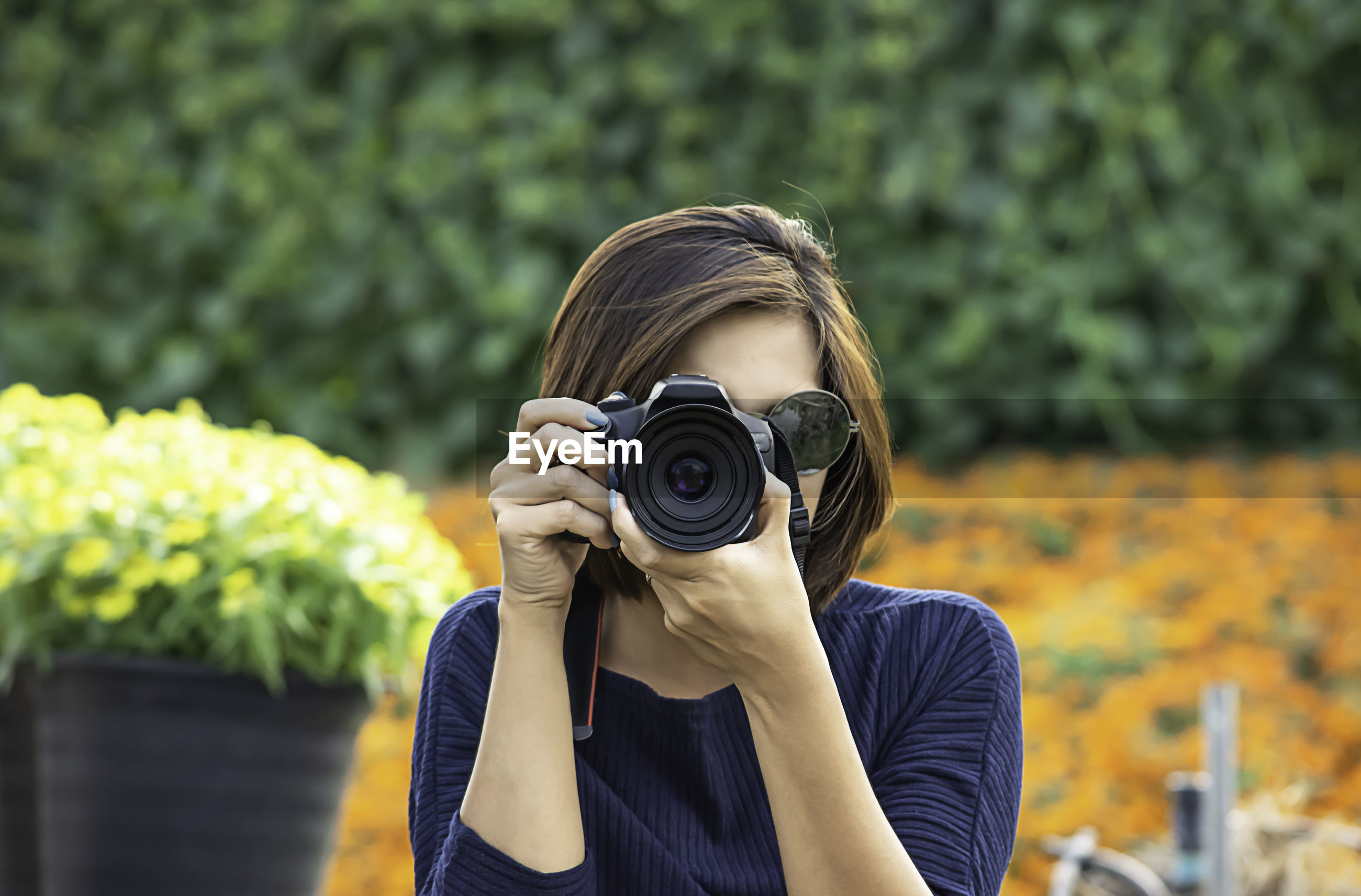 Woman photographing with camera in garden