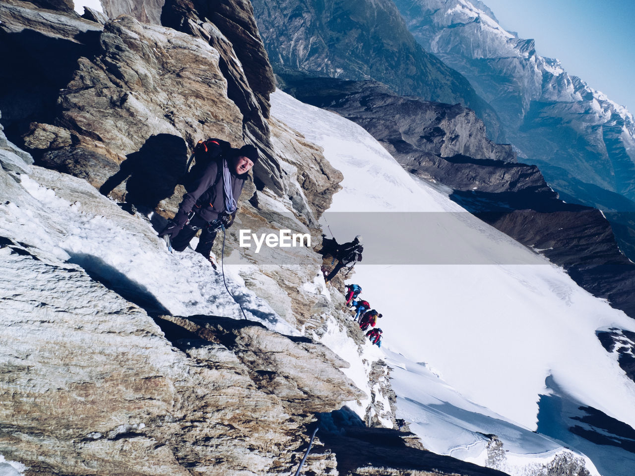 Portrait Of Man Climbing On Snow Covered Rocky Mountain
