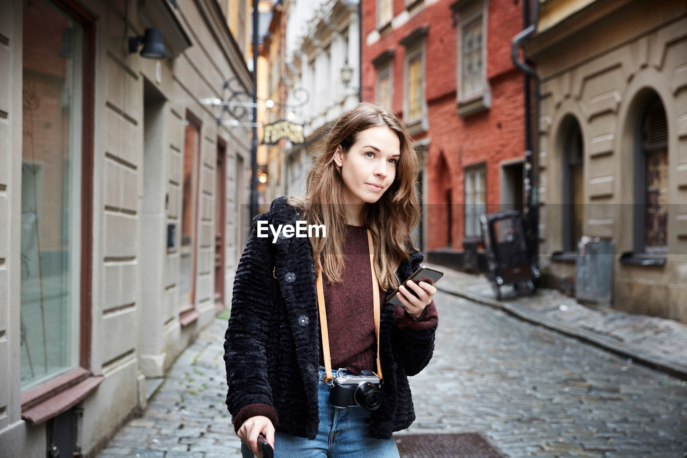 FULL LENGTH PORTRAIT OF WOMAN STANDING ON STREET