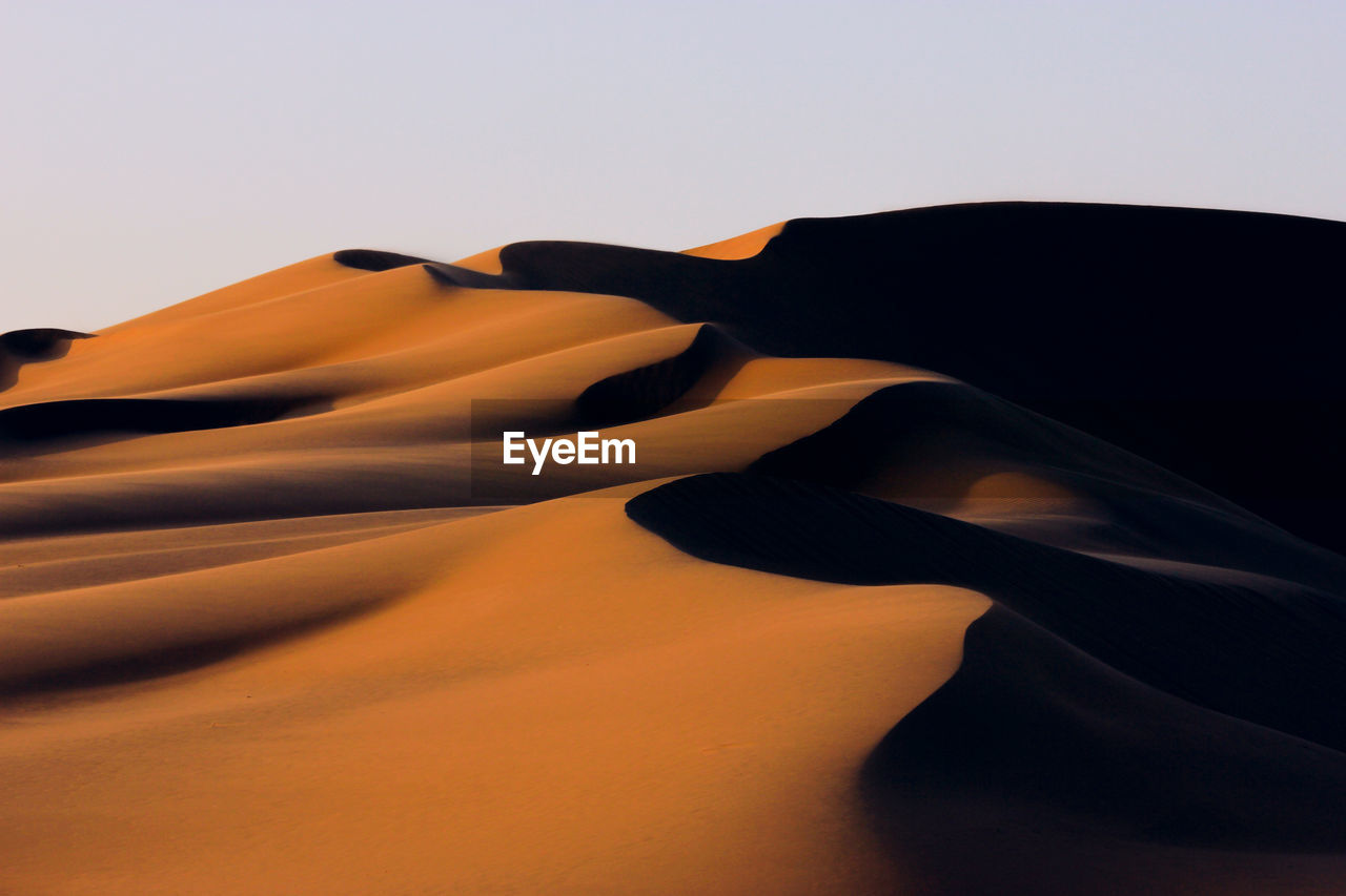 sand dune, sky, desert, environment, sand, scenics - nature, climate, beauty in nature, arid climate, landscape, tranquil scene, nature, tranquility, land, remote, no people, clear sky, non-urban scene, copy space, geology
