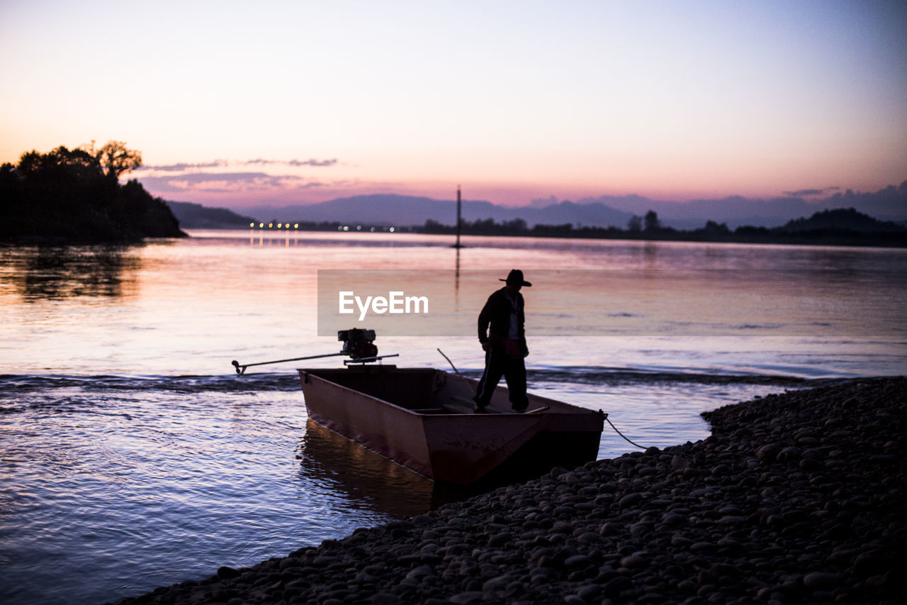 Silhouette of man in a boat during sunset