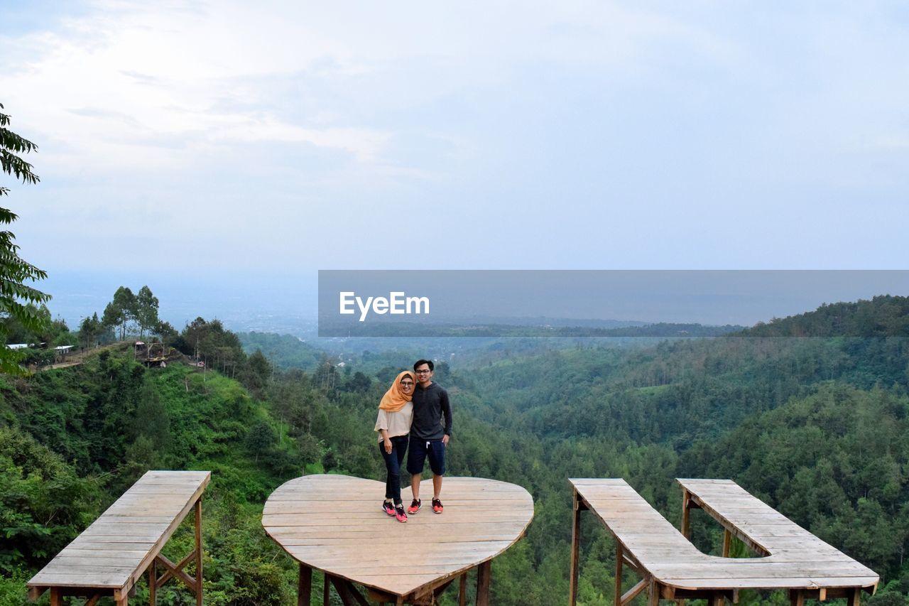 Couple standing on heart shape table against sky