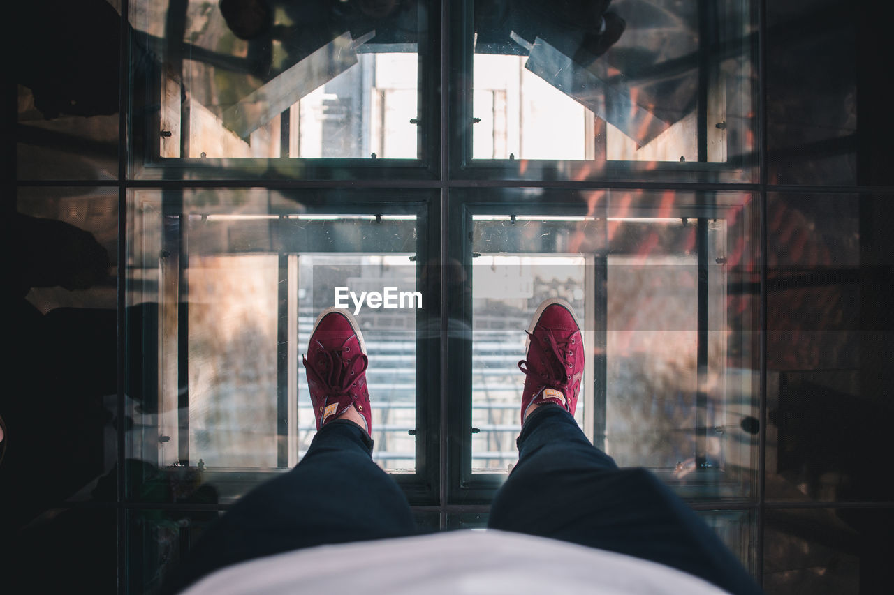 low section, shoe, personal perspective, human leg, human body part, real people, window, body part, one person, indoors, transparent, lifestyles, day, glass - material, unrecognizable person, men, standing, leisure activity, human foot, jeans