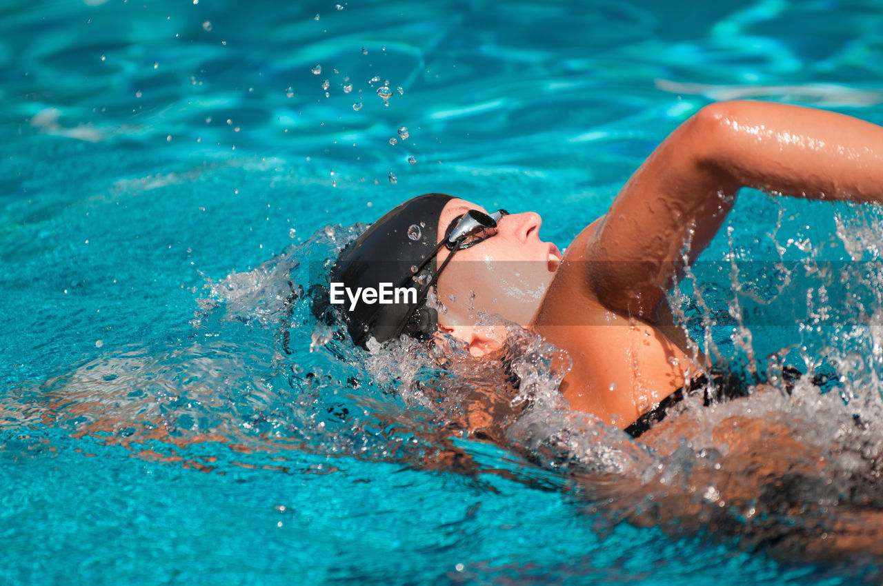 High angle view of mid adult woman swimming in pool