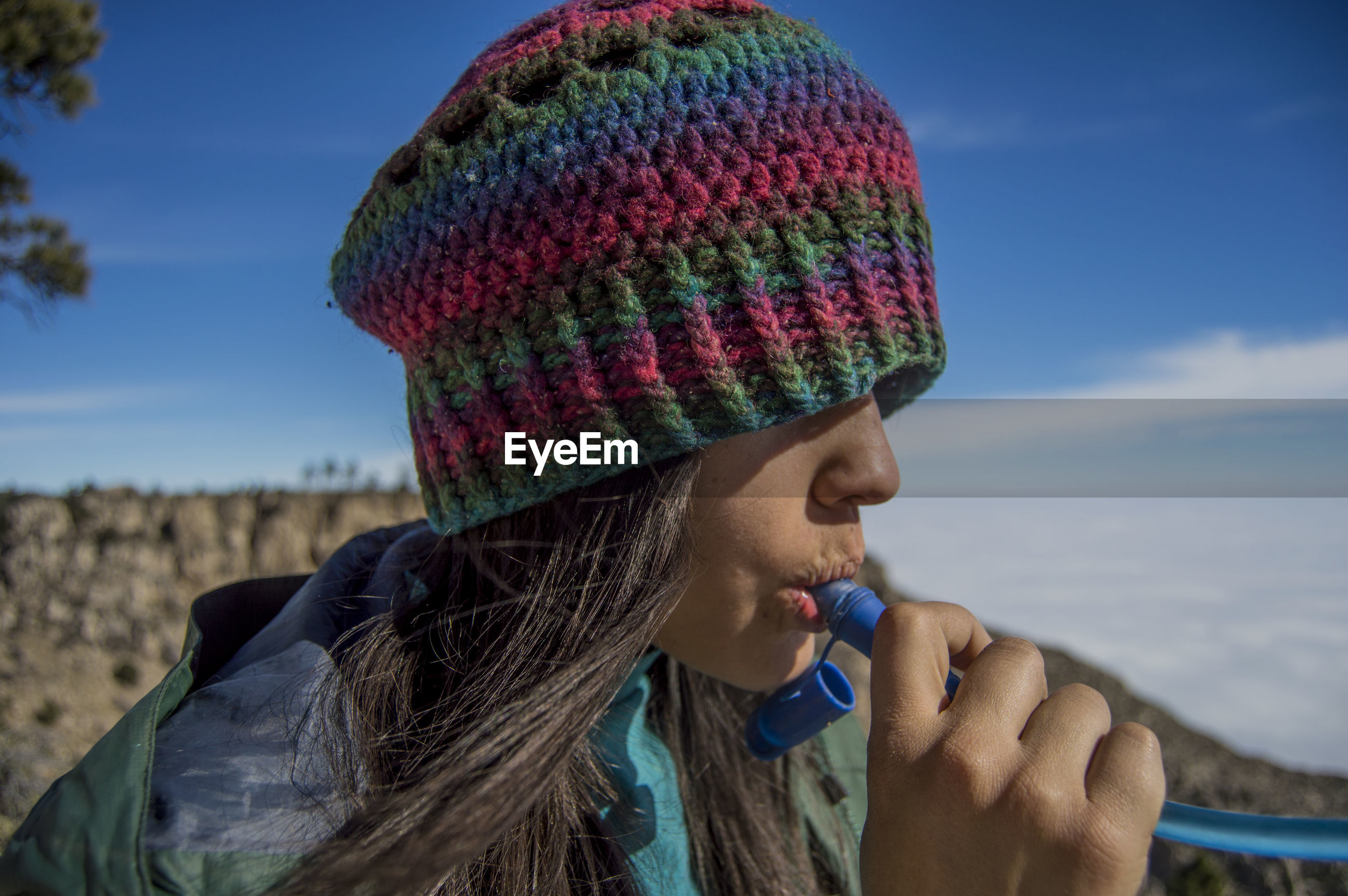 Close-up of woman in knit hat drinking against sky