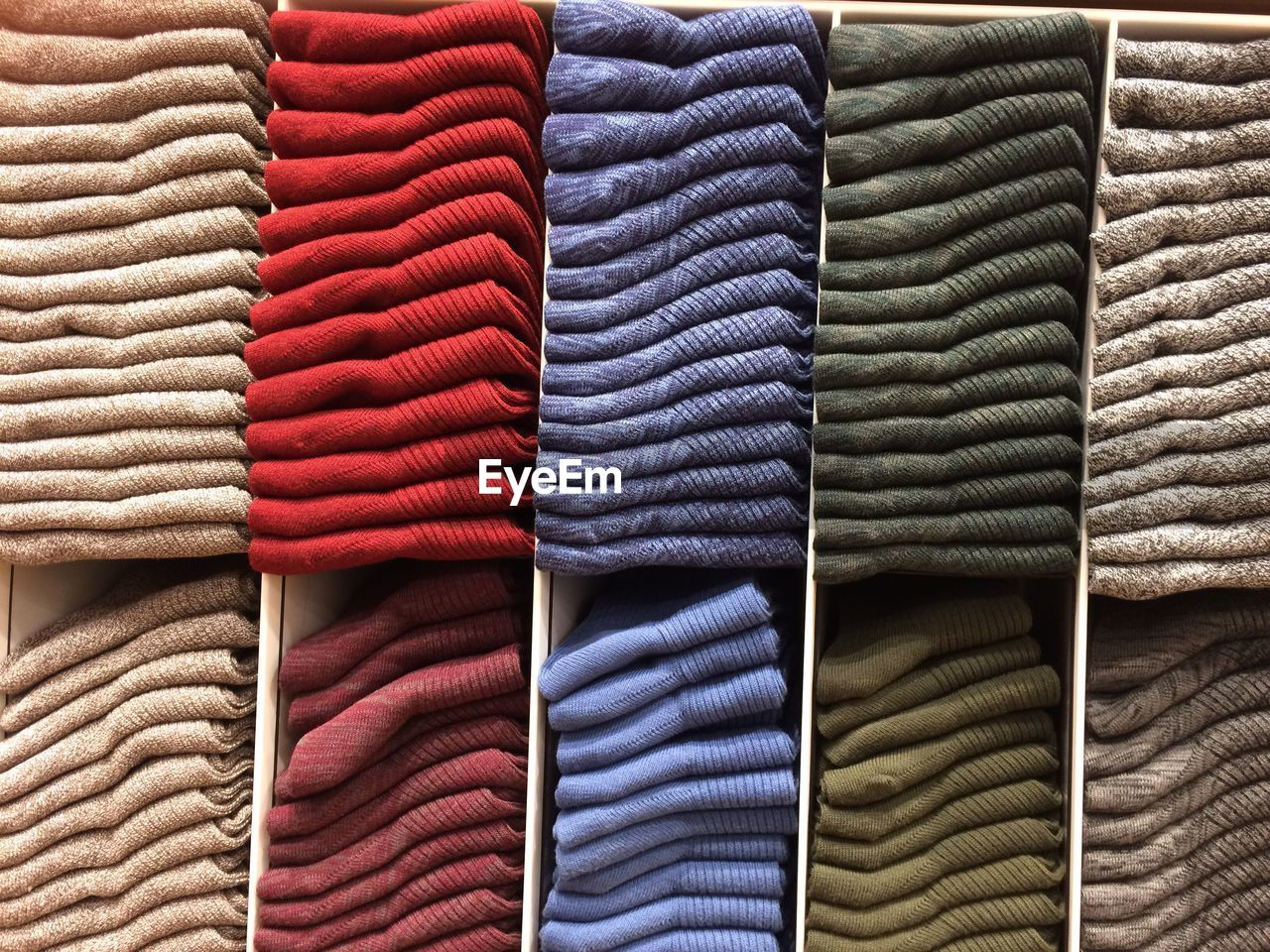 Full frame shot of multi colored sweaters stacked in store