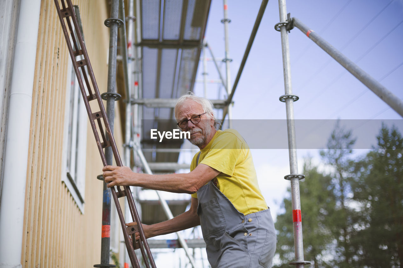 LOW ANGLE VIEW OF MAN WORKING AT POLE