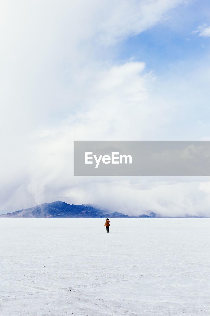Distance Shot Of A Person Walking On Snowed Landscape