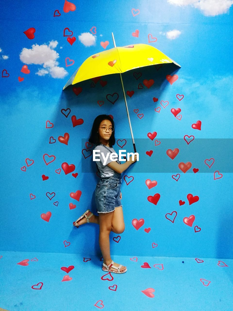 Portrait Of Young Girl Holding Umbrella While Standing Against Blue Wall With Heart Shape