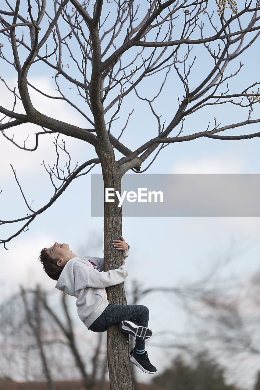 Side View Of Girl Climbing Tree Against Sky