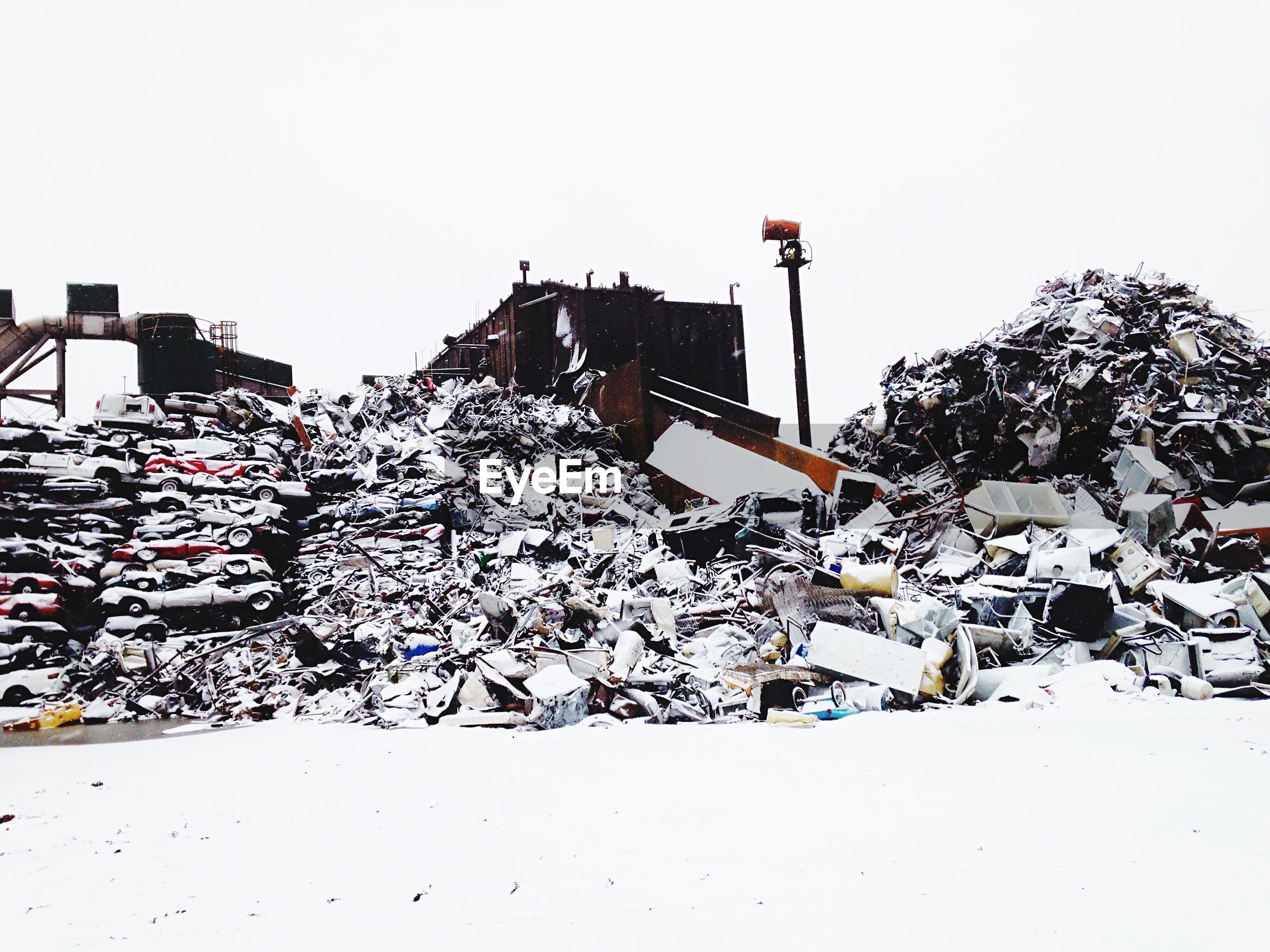 Snow covered junkyard against clear sky