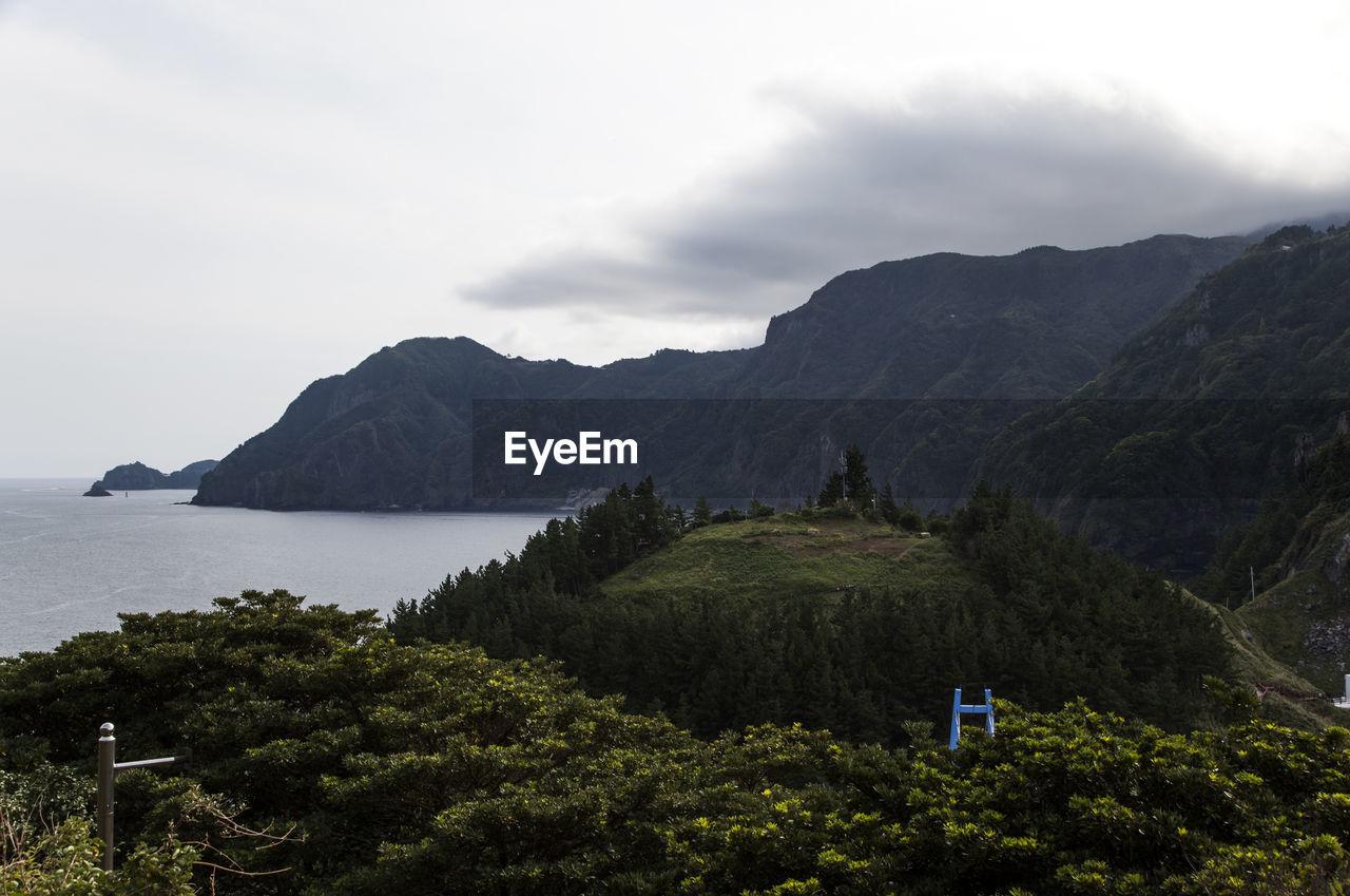Scenic Shot Of Calm Countryside Lake Against Mountain Range