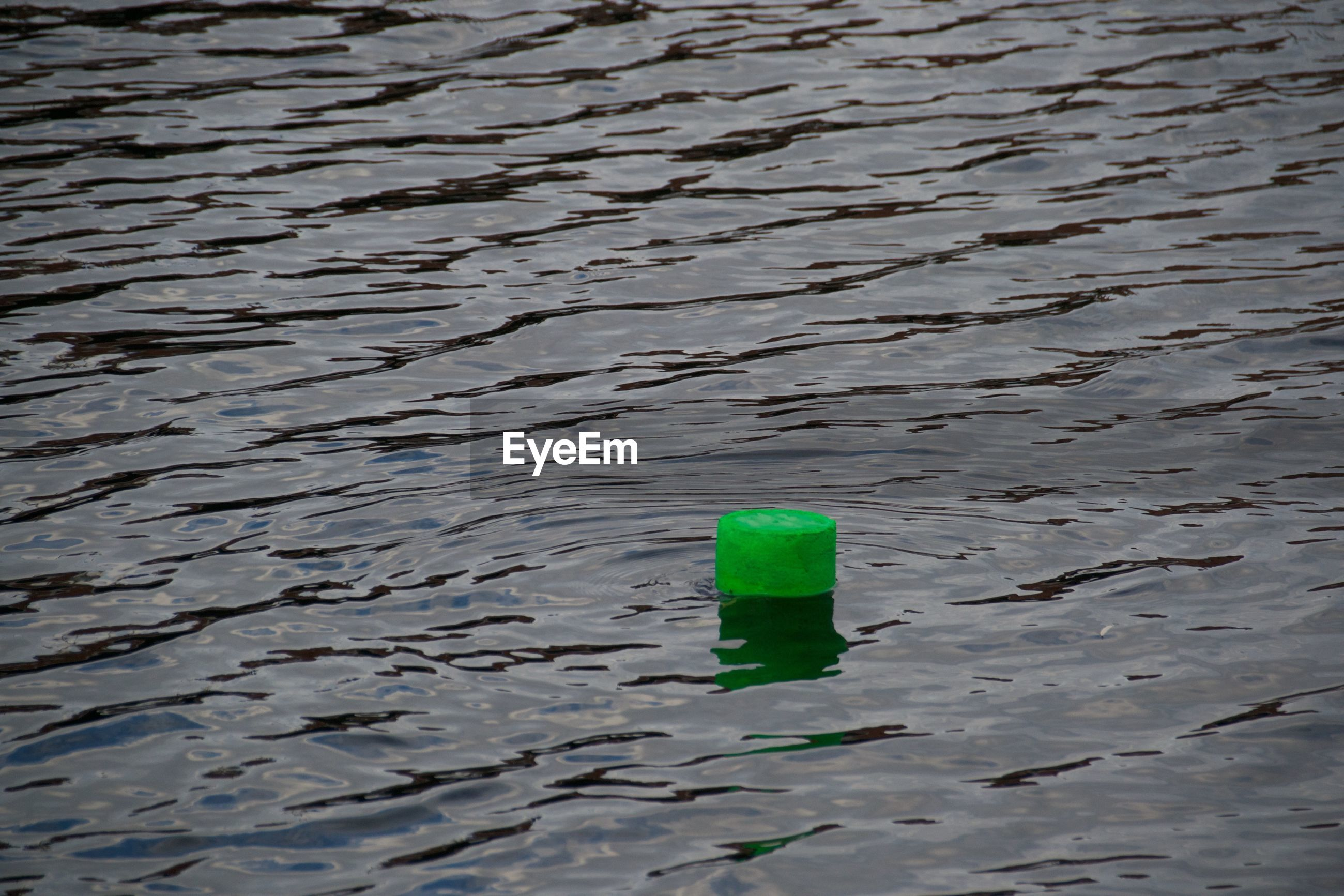 Green buoy floating on water in sea