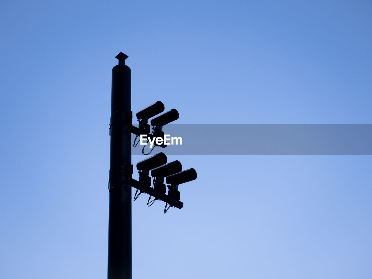 Low Angle View Of Security Cameras On Pole Against Clear Blue Sky