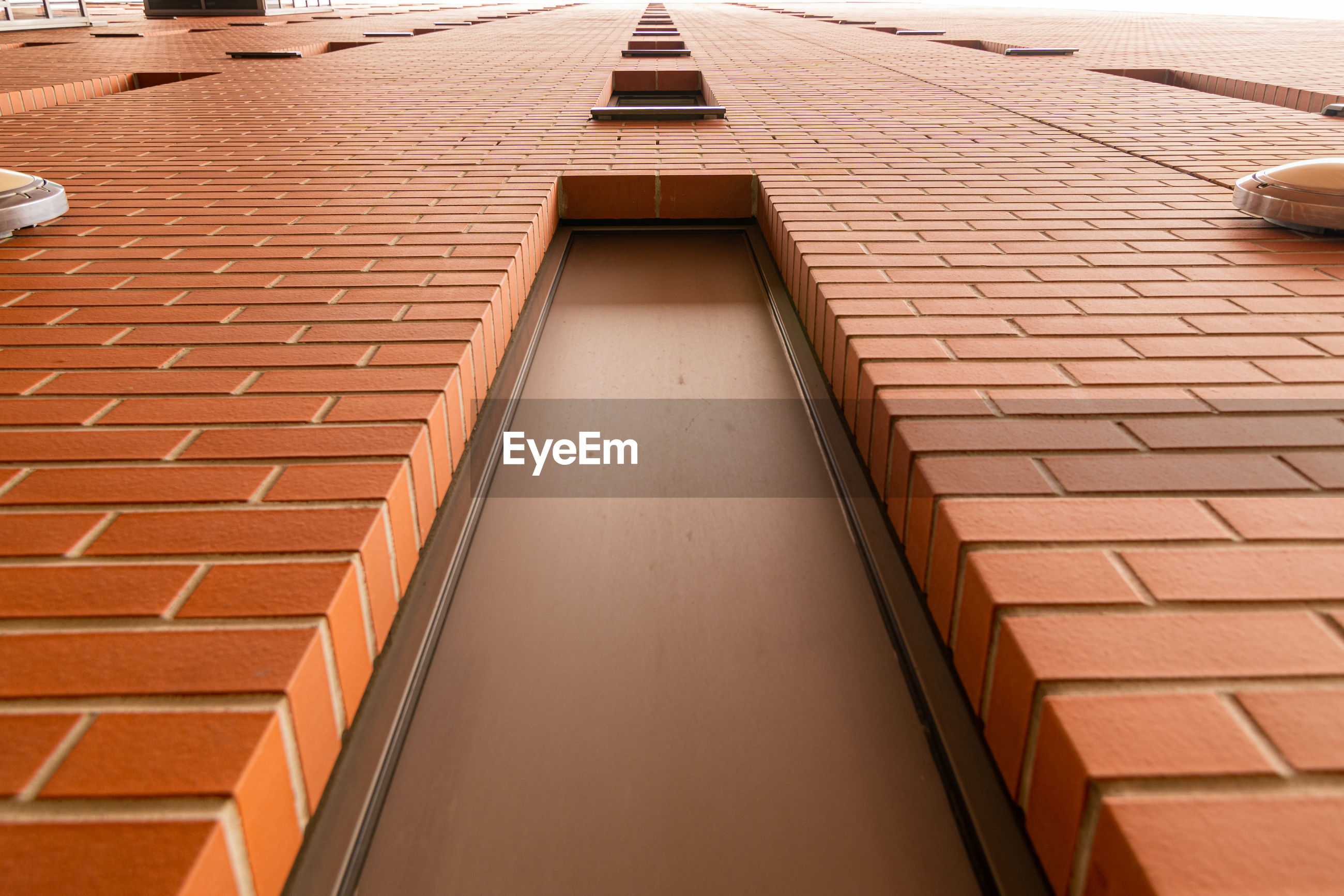 HIGH ANGLE VIEW OF BUILDING ROOF AGAINST BRICK WALL