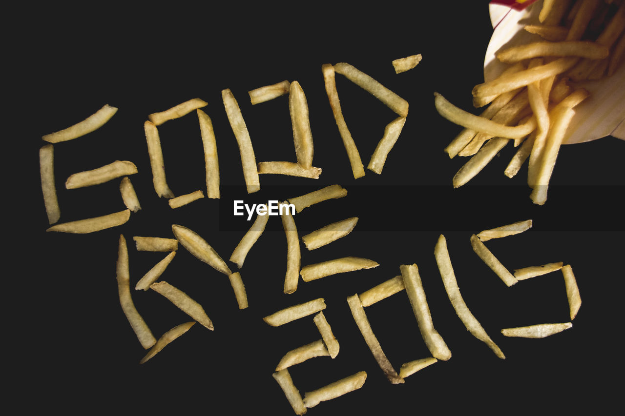 High Angle View Of Text Made From French Fries Over Black Background