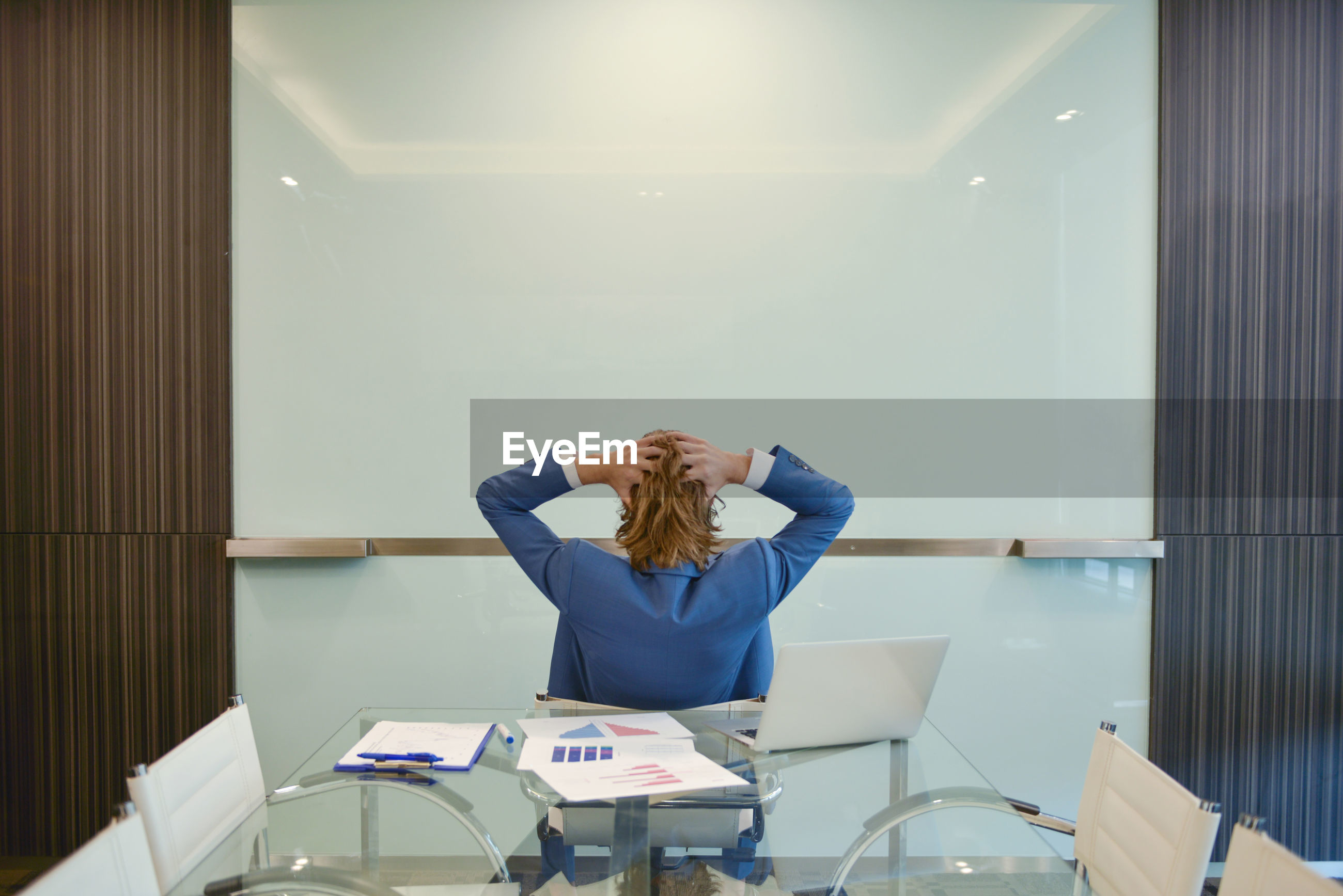 Rear view of businesswoman sitting against desk at office