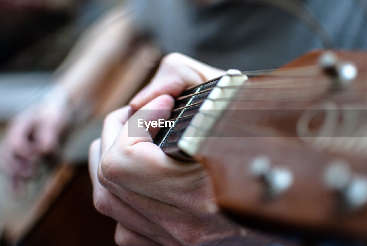 Close-Up Of Male Hands Playing Guitar