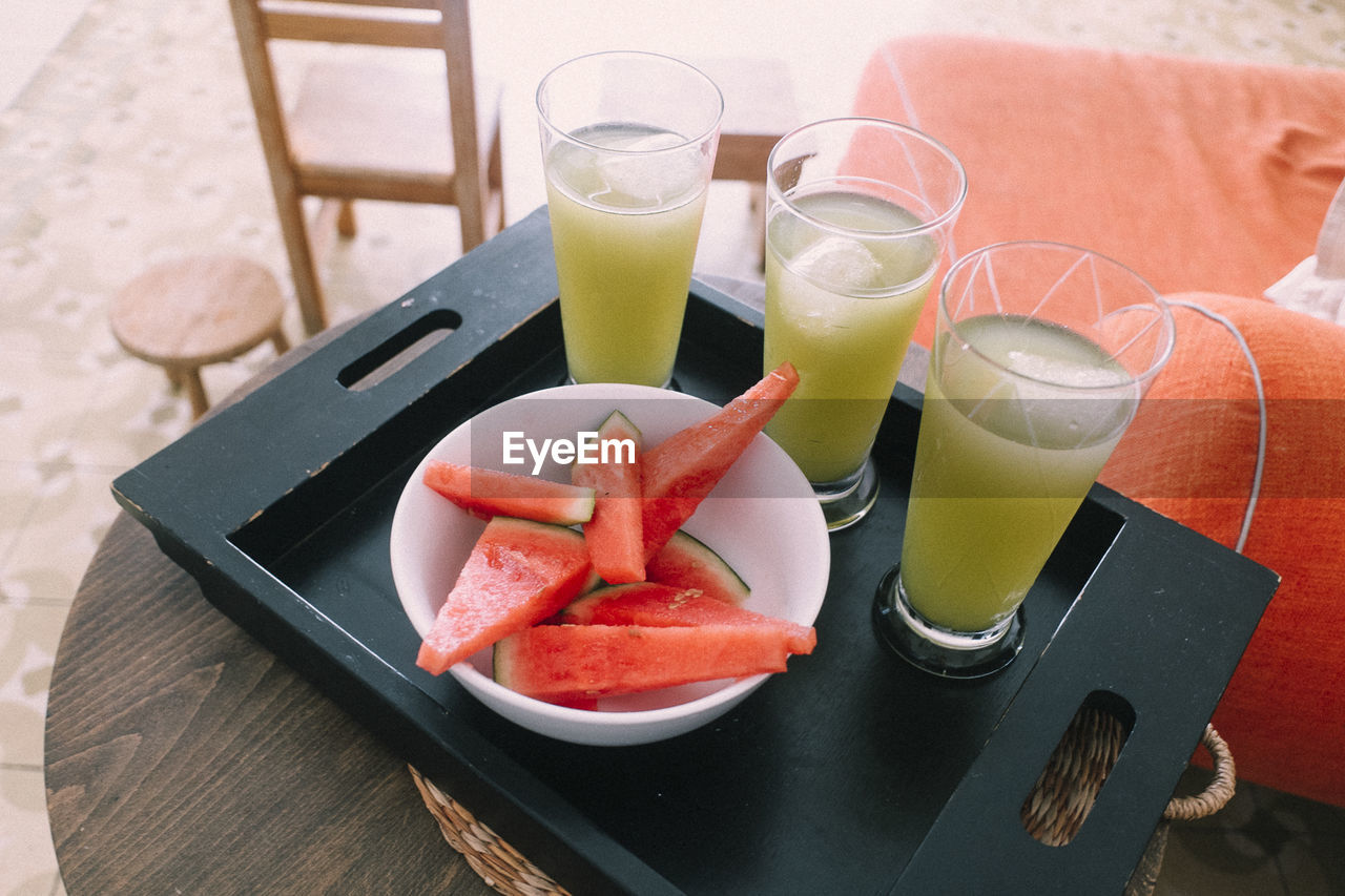High angle view of drinks and watermelon slices served on table