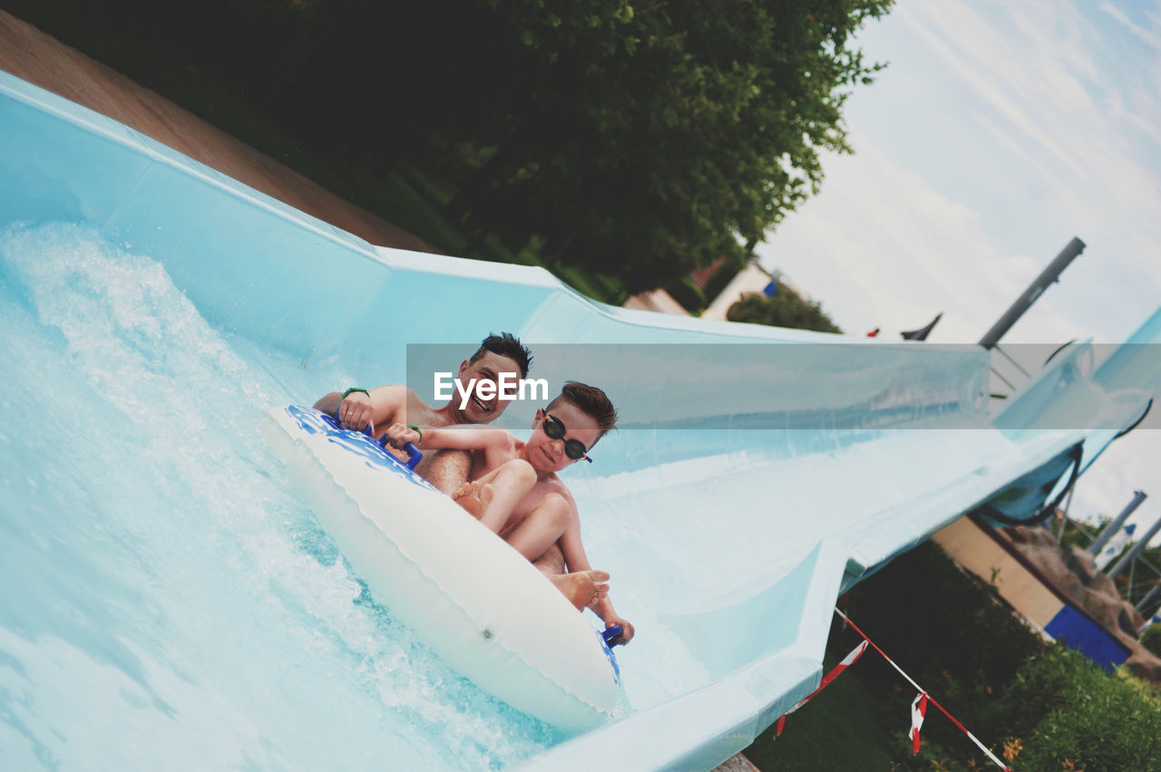 Portrait of happy man with son enjoying on water slide