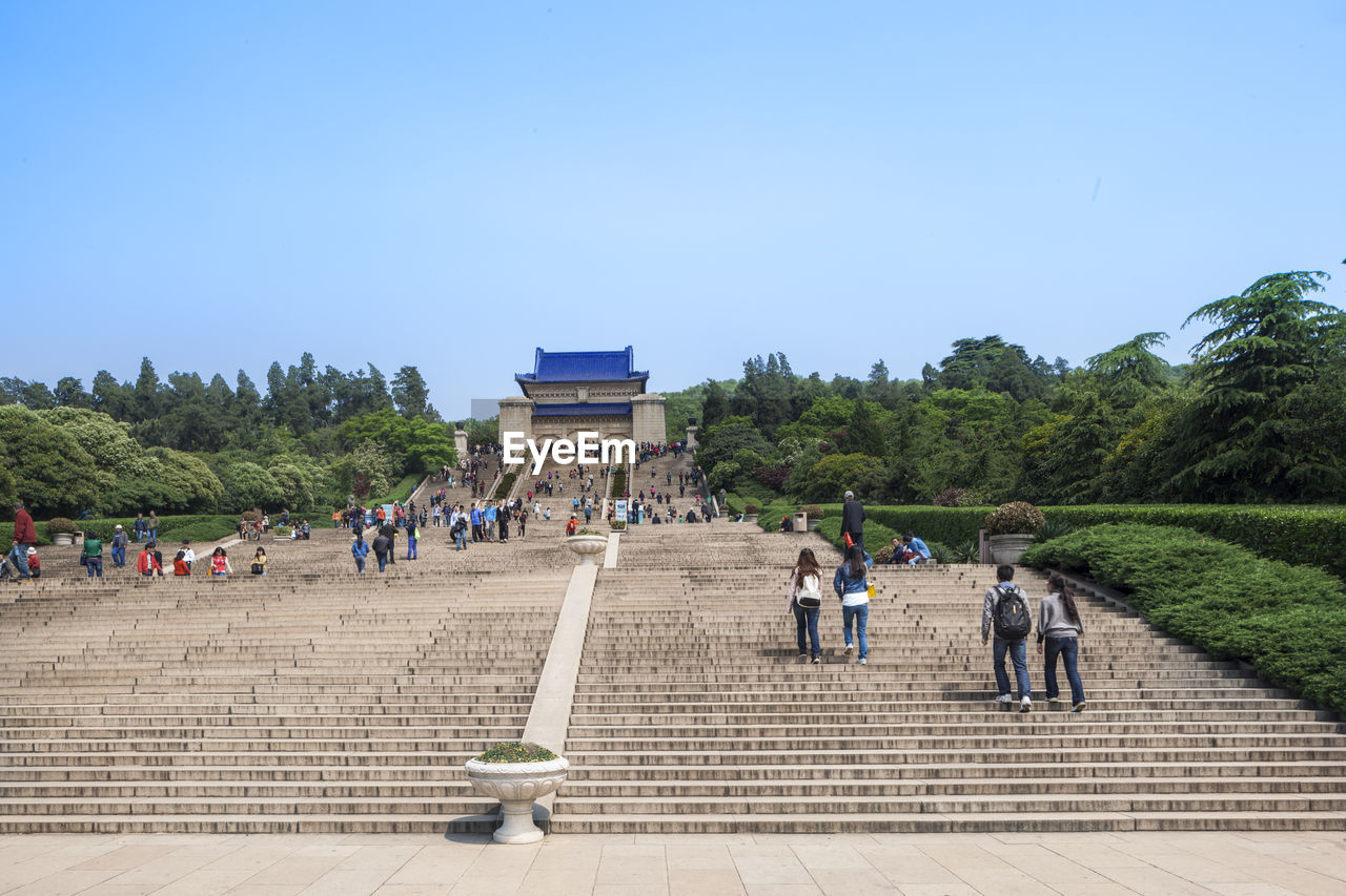 large group of people, real people, travel destinations, history, lifestyles, clear sky, tree, steps, steps and staircases, leisure activity, day, mixed age range, ancient civilization, tourism, built structure, women, men, travel, vacations, ancient, architecture, nature, outdoors, sky, blue, building exterior, people