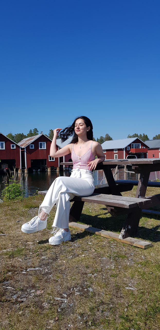 Smiling young woman sitting on bench against sky