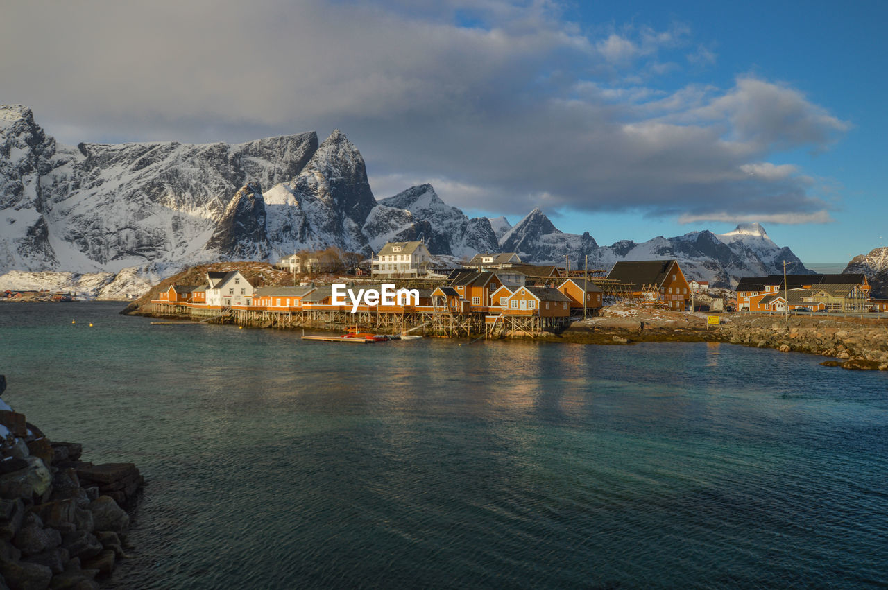 water, sky, architecture, mountain, cloud - sky, built structure, cold temperature, scenics - nature, building exterior, waterfront, beauty in nature, winter, nature, building, no people, snow, lake, tranquil scene, mountain range, outdoors, snowcapped mountain