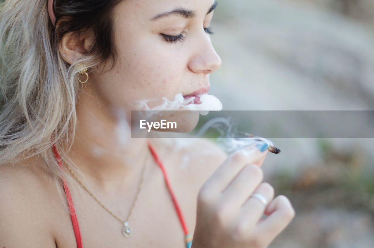 Close-Up Of Woman Smoking Marijuana Joint