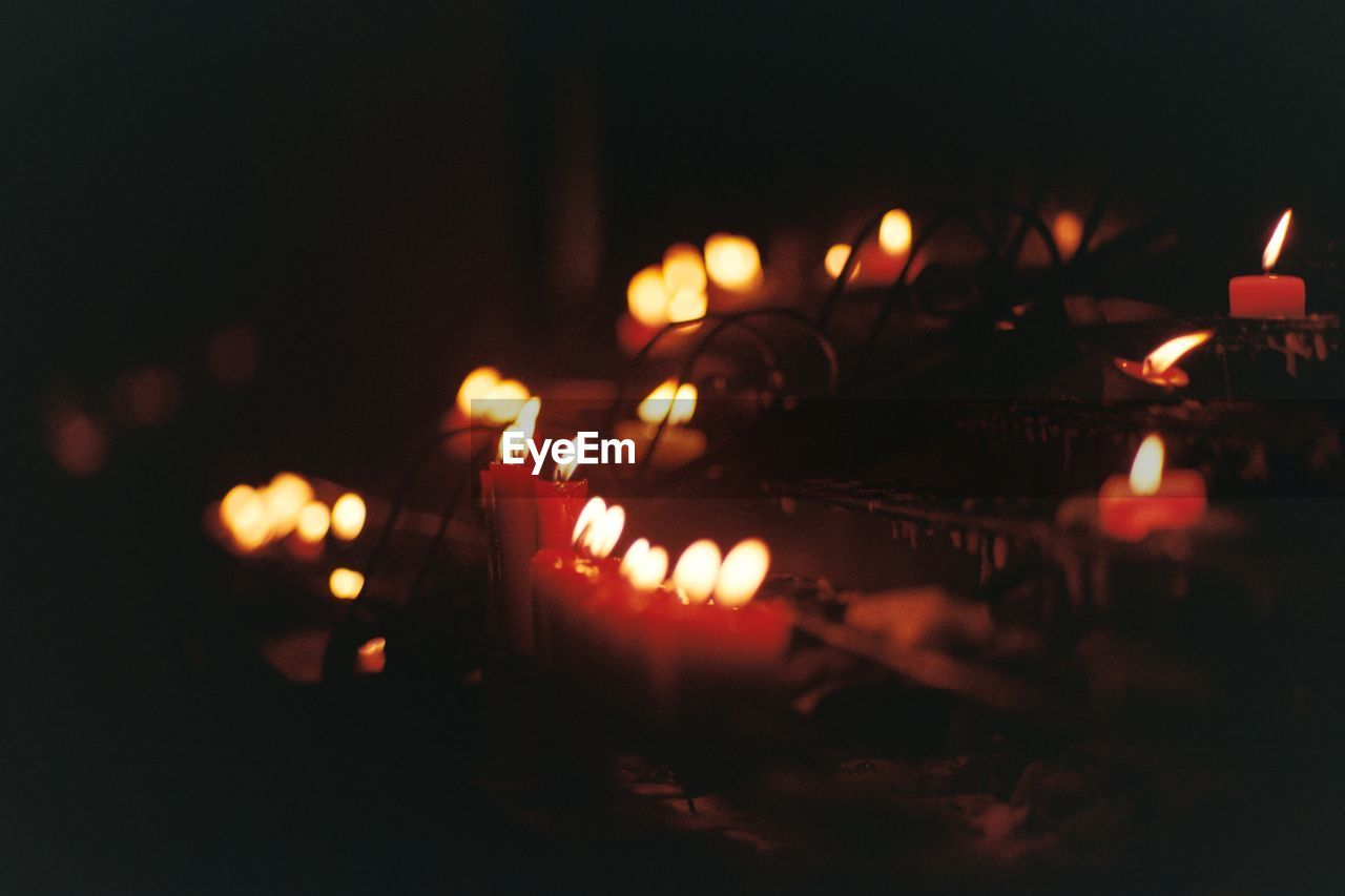Close-up of lit candles burning in temple at night