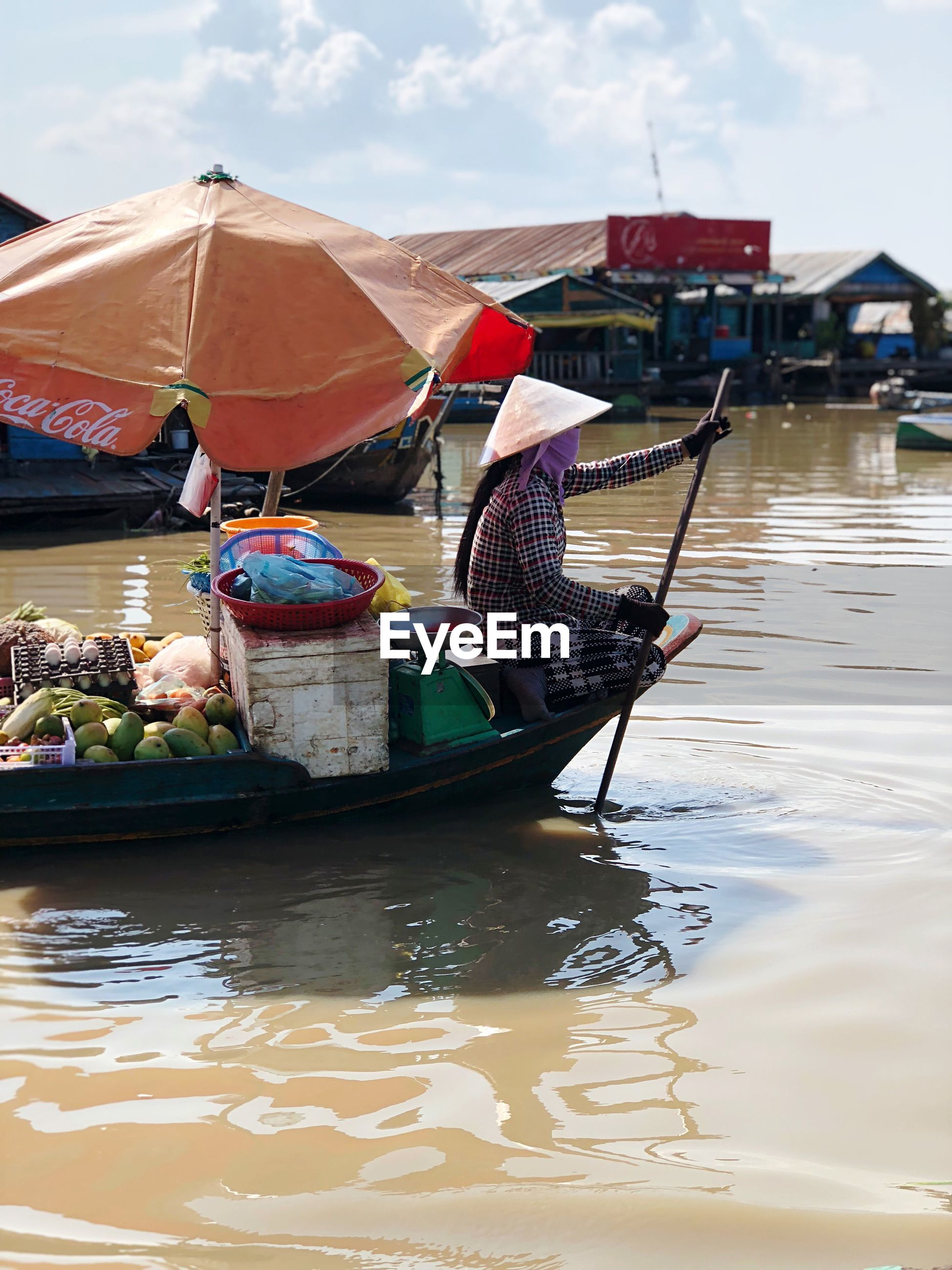 MAN SITTING IN BOATS AT MARKET