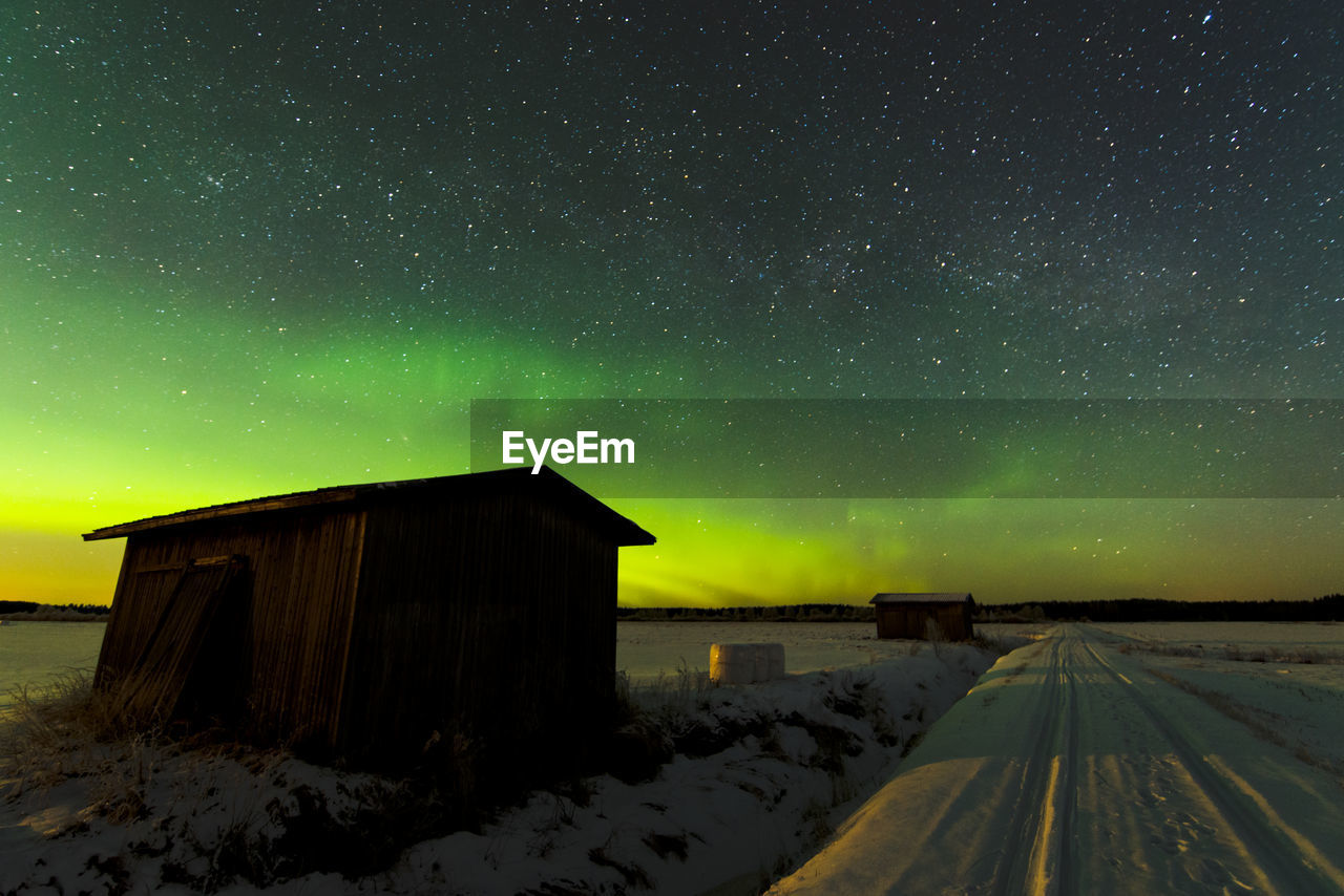 Wooden Houses On Snowcapped Field Against Aurora Borealis In Sky