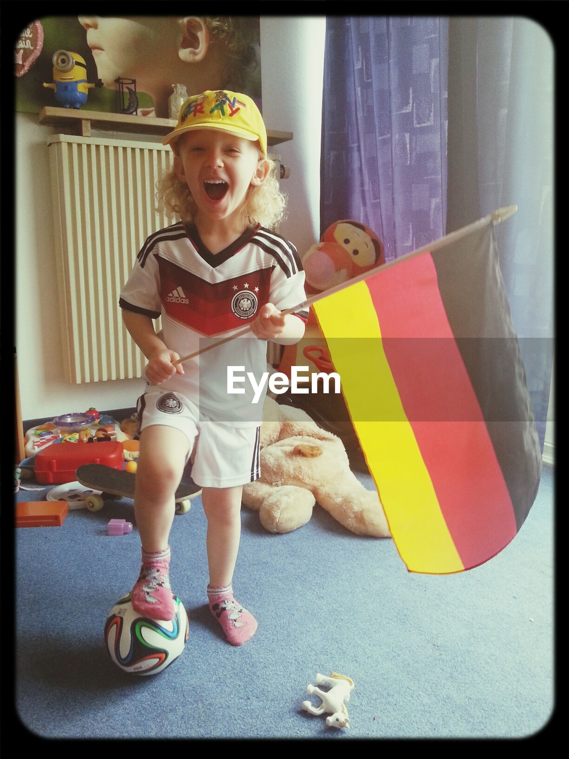 Portrait of playful boy with soccer ball holding german flag at home