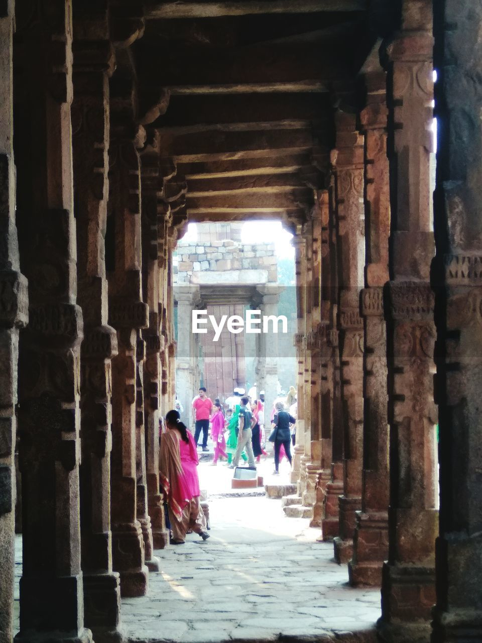 architectural column, built structure, architecture, ancient, walking, indoors, in a row, history, corridor, old ruin, tourism, women, religion, spirituality, travel destinations, travel, place of worship, real people, day, men, ancient civilization, people