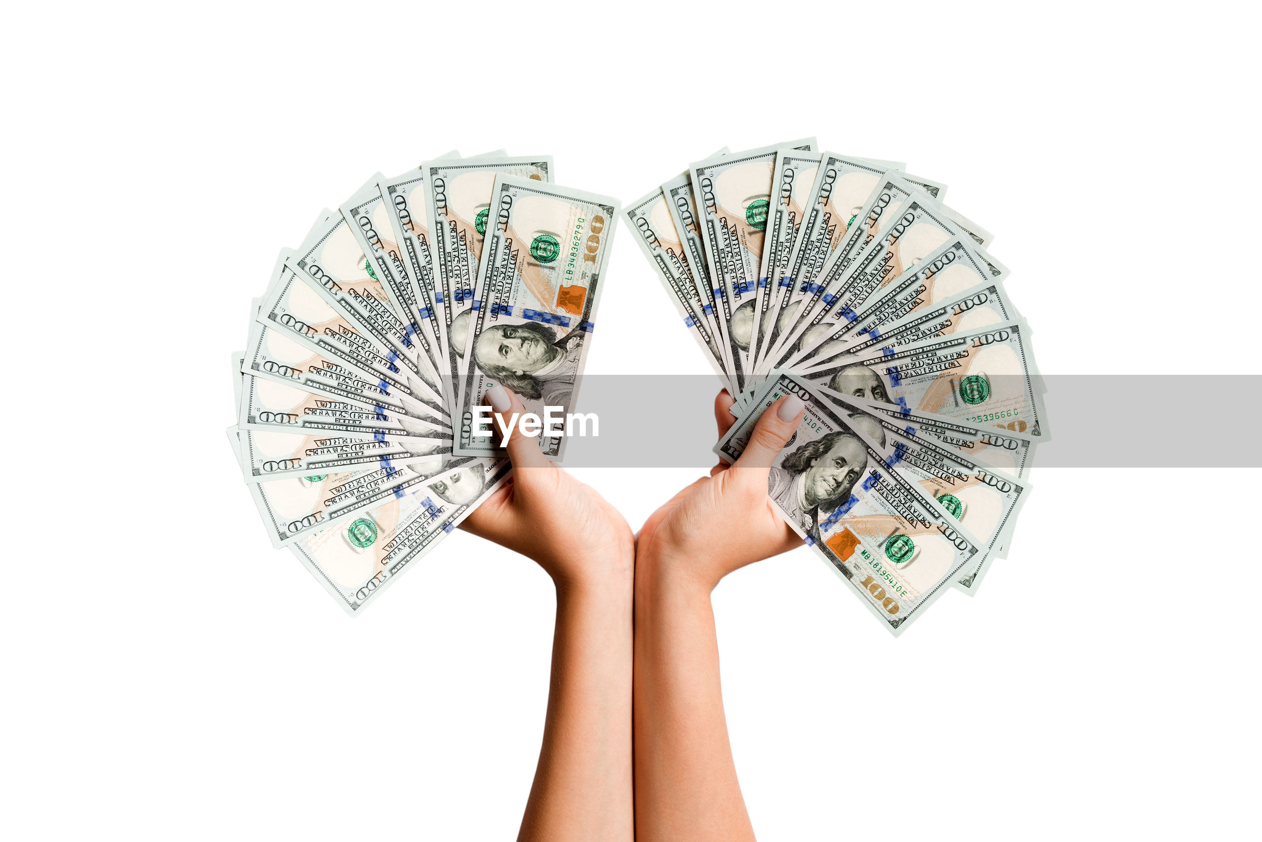 Close-up of hands holding paper currency against white background
