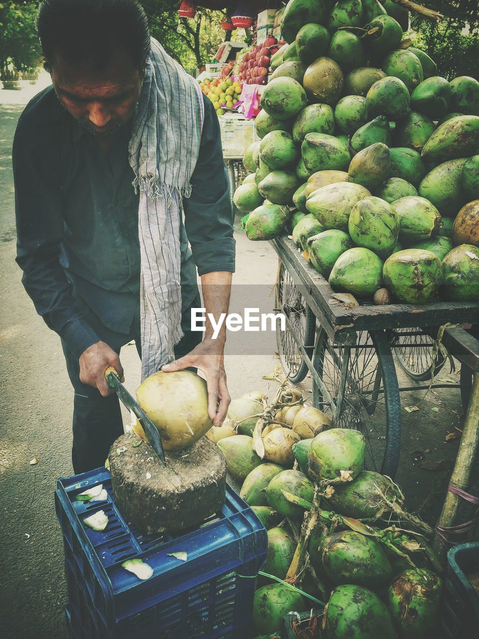 Vendor peeling coconuts at market stall