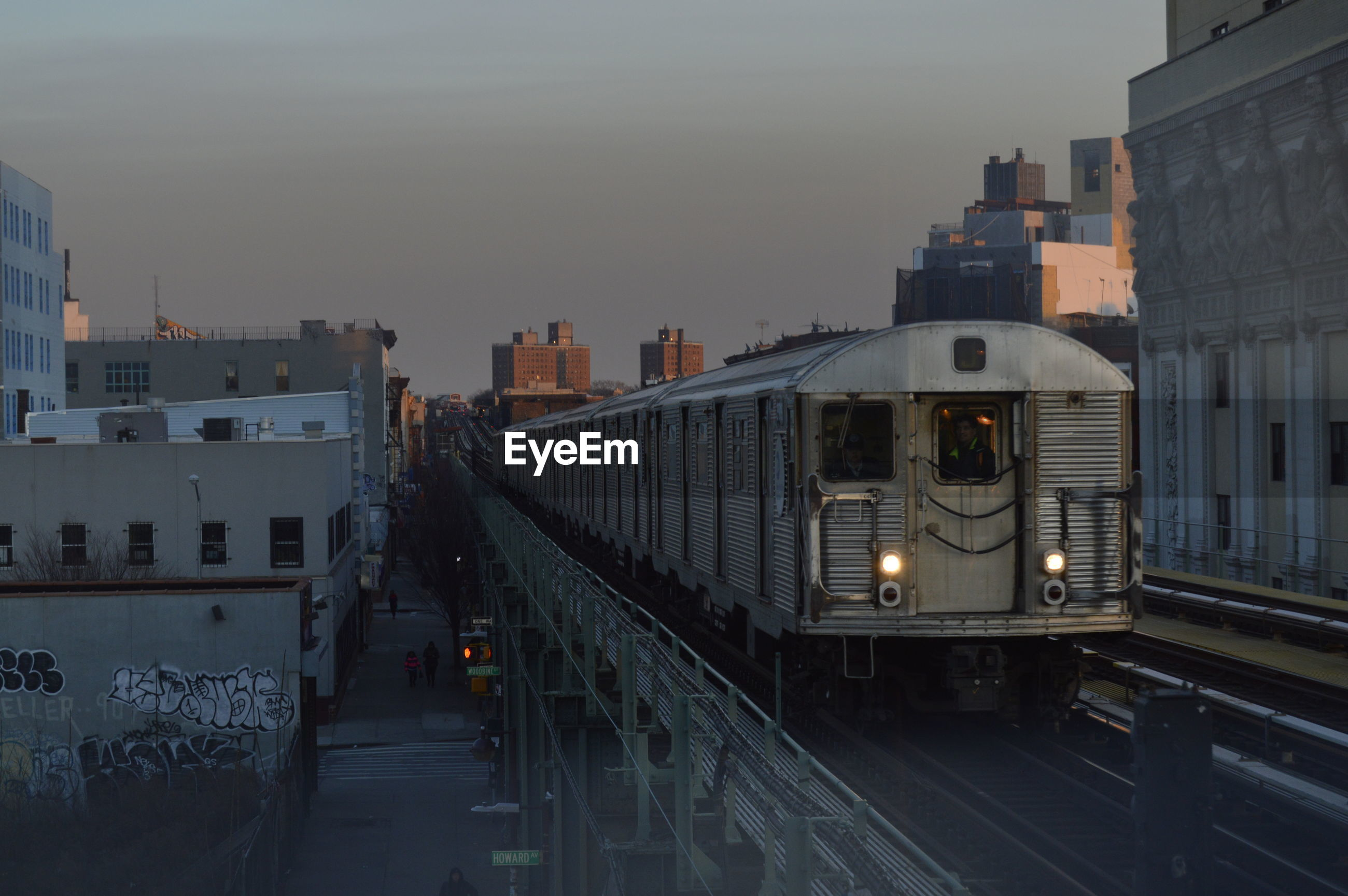 Train against sky in city during sunset